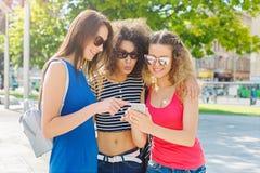 Amis féminins heureux avec le smartphone dehors Image libre de droits
