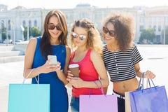 Amis féminins heureux avec le smartphone dehors Photo stock