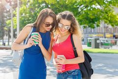 Amis féminins heureux avec le smartphone dehors Photos stock