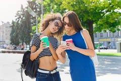 Amis féminins heureux avec le smartphone dehors Photographie stock