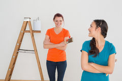 Amis féminins heureux avec les pinceaux et l'échelle Photographie stock libre de droits