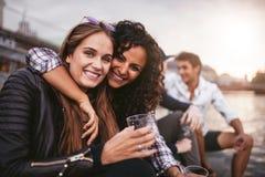 Amis féminins heureux ayant l'amusement avec des boissons sur le lac Photographie stock libre de droits