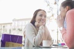 Amis féminins heureux bavardant au café extérieur Photos stock