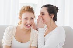 Amis féminins heureux bavardant dans le salon Photographie stock libre de droits