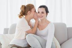 Amis féminins heureux bavardant dans le salon Images stock