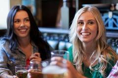 Amis féminins heureux buvant de la bière à la barre ou au bar Images libres de droits