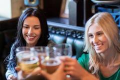 Amis féminins heureux buvant de la bière à la barre ou au bar Photo stock