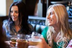 Amis féminins heureux buvant de la bière à la barre ou au bar Image libre de droits