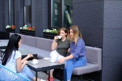 Amis féminins heureux buvant du café et s'asseyant au café Image stock