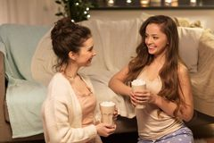Amis féminins heureux buvant le cacao à la maison Photographie stock