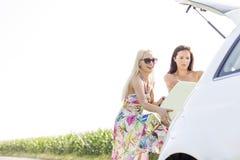 Amis féminins heureux chargeant le bagage dans le tronc de voiture contre le ciel clair Image libre de droits