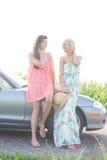 Amis féminins heureux conversant tout en se tenant prêt le convertible contre le ciel clair Photographie stock