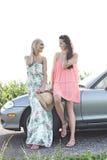 Amis féminins heureux conversant tout en se tenant prêt le convertible contre le ciel clair Image stock