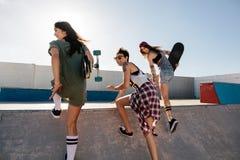 Amis féminins heureux courant au-dessus de la rampe de planche à roulettes Photographie stock libre de droits