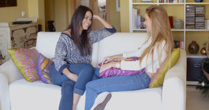 Amis féminins heureux détendant et causant Image stock