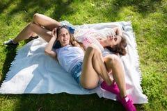 Amis féminins heureux détendant sur la couverture en parc Photo stock