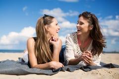 Amis féminins heureux détendant sur parler de plage Images stock