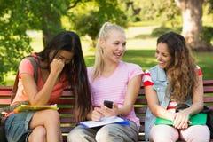 Amis féminins heureux d'université s'asseyant sur le banc de campus Image libre de droits