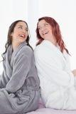 Amis féminins heureux dans des peignoirs se reposant de nouveau au dos sur le lit Photo libre de droits