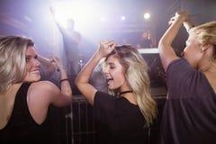 Amis féminins heureux dansant à la boîte de nuit Photo stock