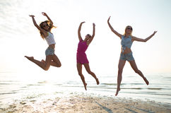 Amis féminins heureux dansant et sautant sur la plage Photo stock