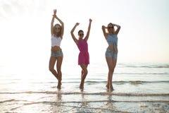 Amis féminins heureux dansant sur la plage Image stock