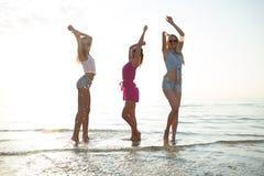 Amis féminins heureux dansant sur la plage Photographie stock libre de droits
