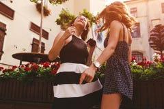 Amis féminins heureux dansant tout en écoutant la musique dehors Images stock