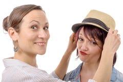 Amis féminins heureux essayant des chapeaux Photos libres de droits