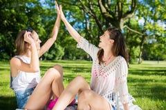 Amis féminins heureux faisant l'extérieur de la haute cinq Photo stock