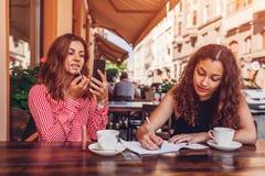 Amis féminins heureux faisant le maquillage tout en ayant le café et faisant le travail en café extérieur Étudiantes écrivant des Photographie stock libre de droits