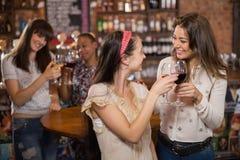 Amis féminins heureux grillant des verres à vin Photo stock