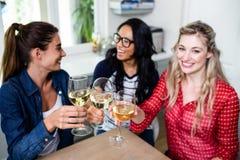 Amis féminins heureux grillant le verre à vin à la table Photos stock