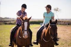 Amis féminins heureux intégraux parlant tandis qu'équitation Photo stock