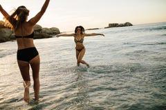 Amis féminins heureux jouant à la plage Images libres de droits