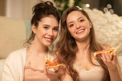 Amis féminins heureux mangeant de la pizza à la maison Images stock