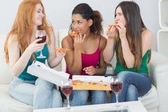 Amis féminins heureux mangeant de la pizza avec du vin à la maison Photo stock