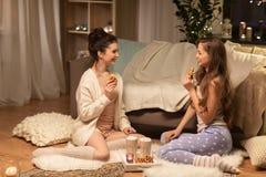 Amis féminins heureux mangeant des gaufres à la maison Photo stock