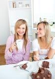 Amis féminins heureux mangeant un gâteau et un boire Photographie stock