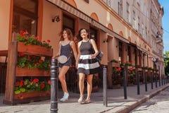 Amis féminins heureux marchant le long de vieilles rues de ville en été et tenant des mains Image libre de droits