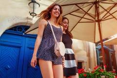 Amis féminins heureux marchant le long de vieilles rues de ville en été Filles ayant l'amusement Images stock