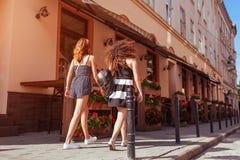 Amis féminins heureux marchant le long de vieilles rues de ville en été Vue arrière Photographie stock libre de droits