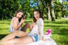 Amis féminins heureux montrant des pouces se reposant dehors Image libre de droits