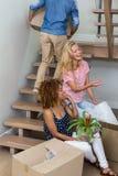 Amis féminins heureux par le carton dans la nouvelle maison Images libres de droits