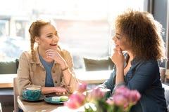 Amis féminins heureux parlant en café Photos stock