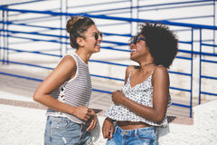 Amis féminins heureux parlant et riant Photo stock
