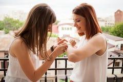 Amis féminins heureux parlant et riant du balcon Photographie stock