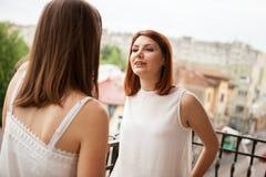 Amis féminins heureux parlant et riant du balcon Photos libres de droits