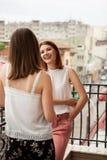 Amis féminins heureux parlant et riant du balcon Images stock