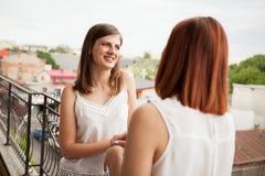 Amis féminins heureux parlant et riant du balcon Photo stock